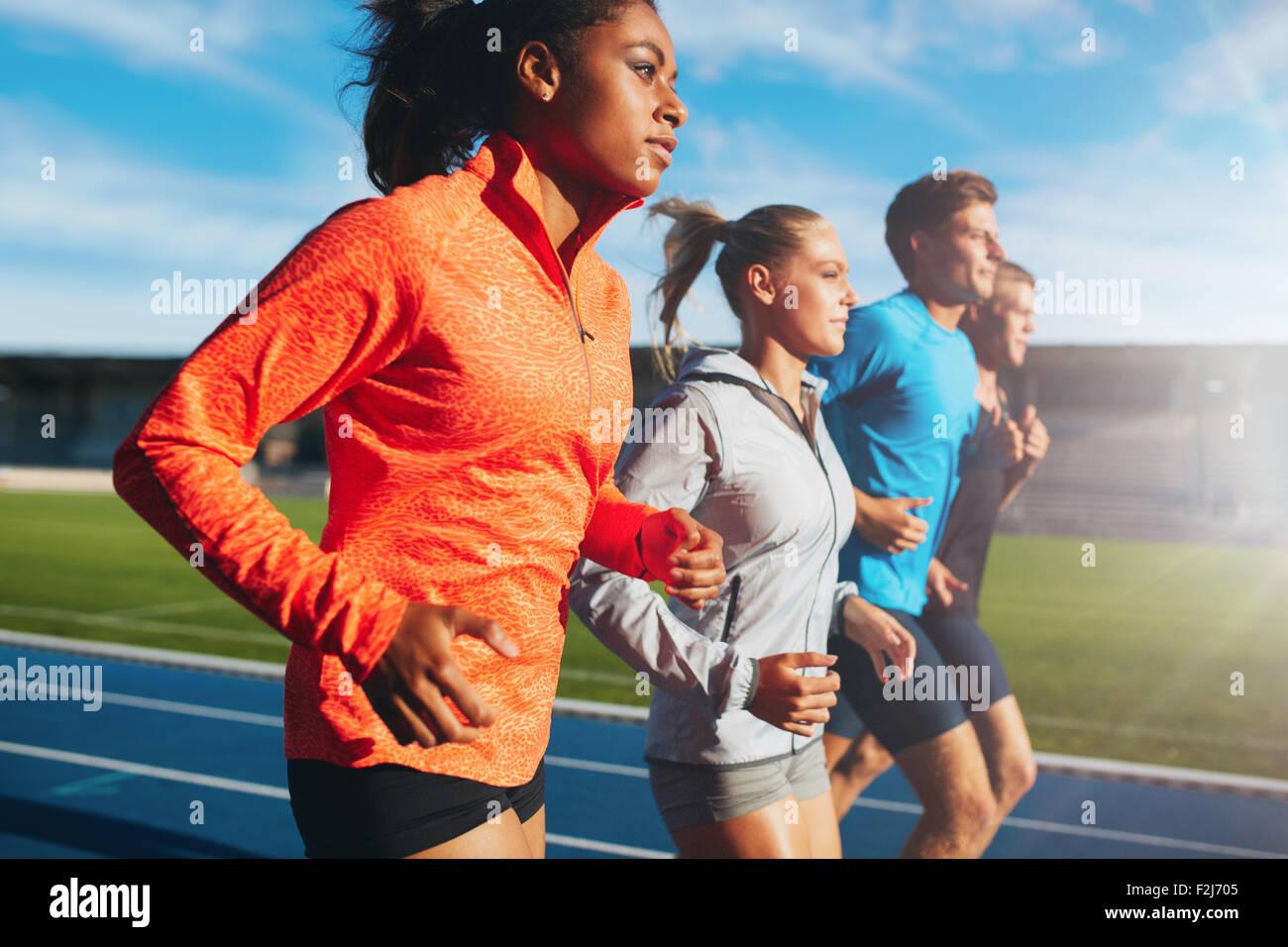 Joven africana corriendo con su equipo en la pista de atletismo en el estadio. Equipo multirracial de corredor que Imagen De Stock