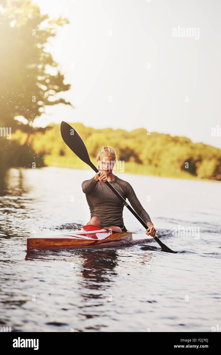 Athletic joven mujer rubia sentada en el kayak mientras remando con un remo de doble hoja sobre la superficie de Imagen De Stock