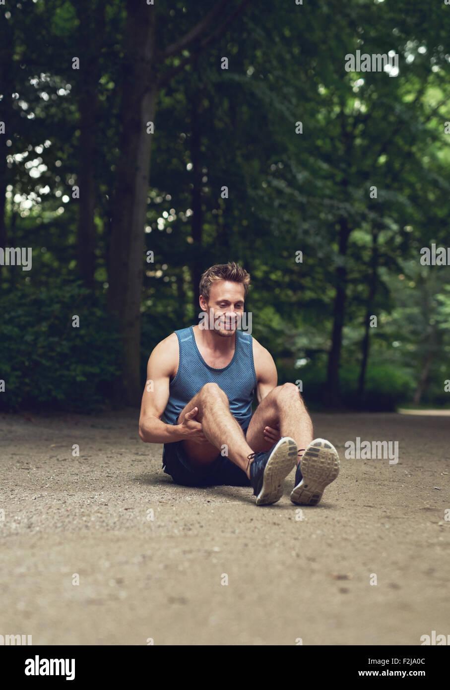 Athletic hombre joven sentado en el suelo en el parque y flexionando sus piernas como ejercicio de calentamiento, Imagen De Stock