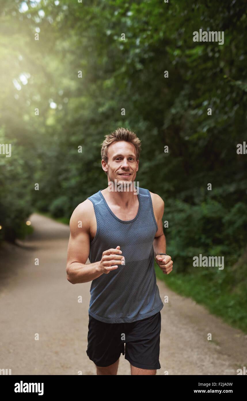 Disparo de tres cuartos de un joven atlético hombre corriendo en el parque en la mañana. Imagen De Stock