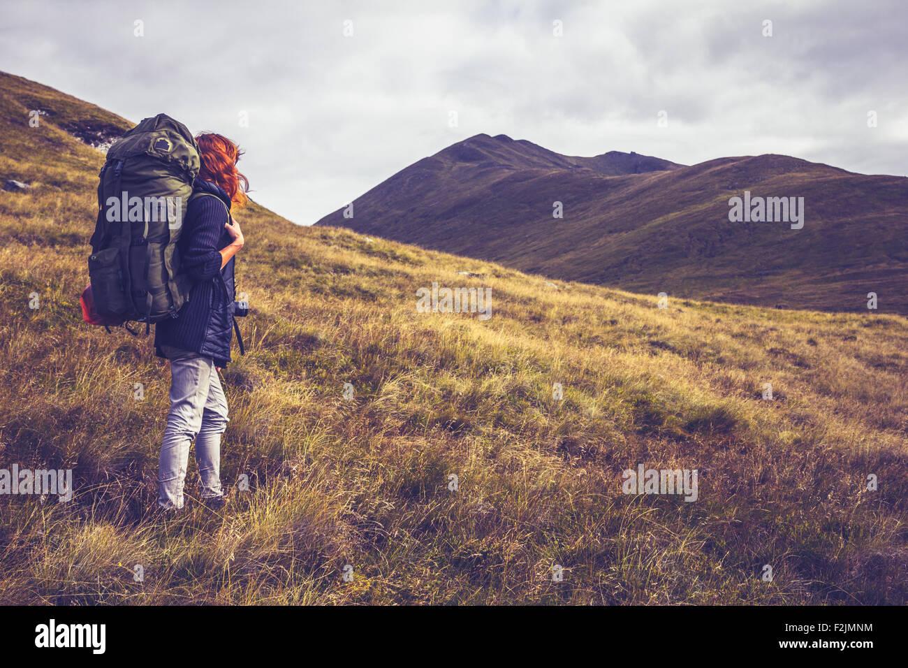 Mujer joven mochilero a través del desierto con montañas Imagen De Stock