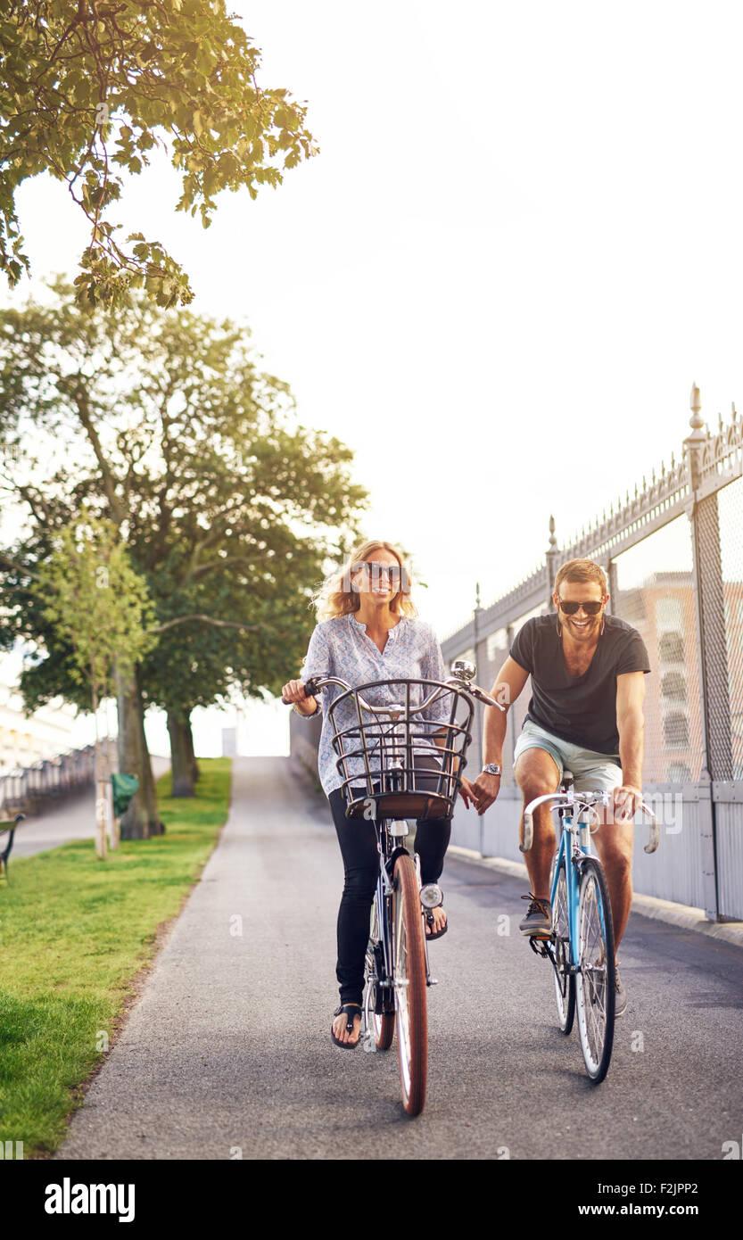 Pareja romántica en bicicleta a lo largo de un ciclo ruta en un parque urbano tomados de la mano y sonriendo Imagen De Stock