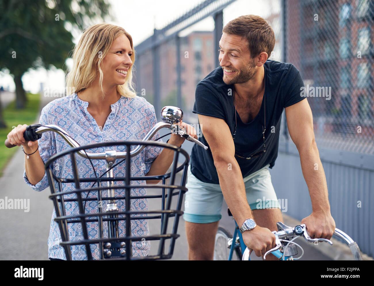 Pareja joven ligar como conversan en una calle urbana, en sus bicicletas sonriendo y mirando en cada otros ojos, Imagen De Stock