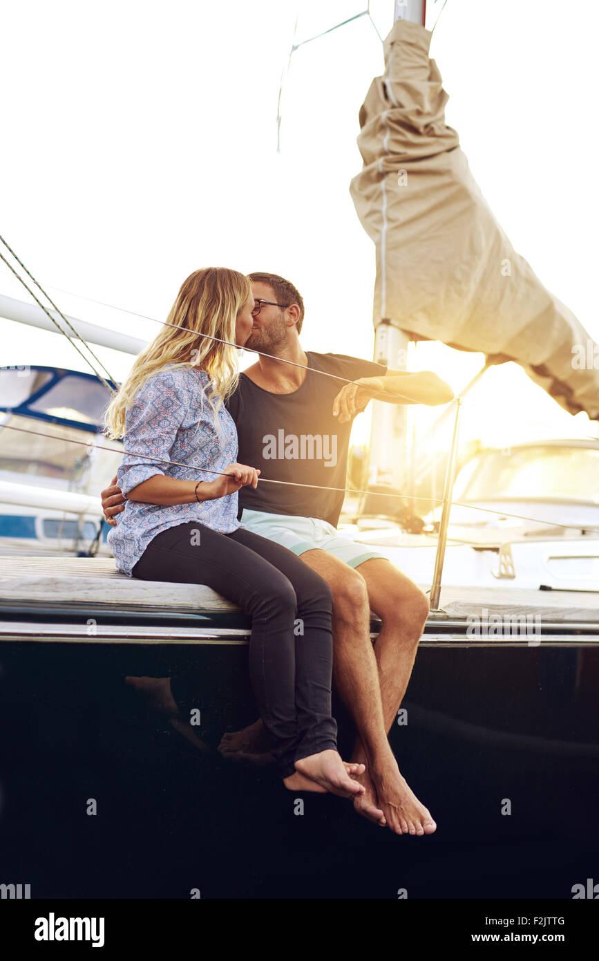 Dulce joven pareja besándose en la cubierta del yate durante la puesta de sol. Imagen De Stock