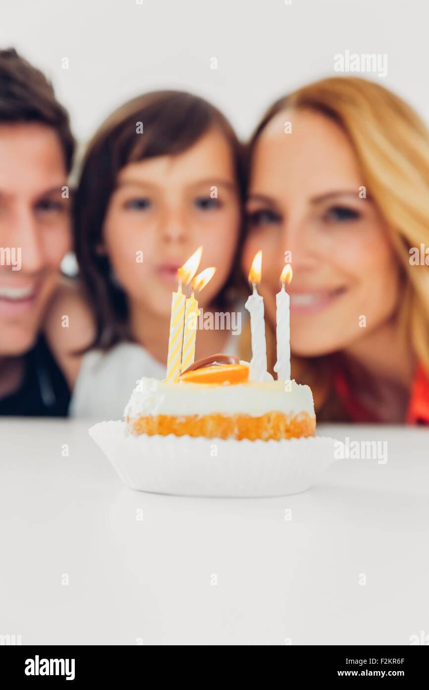 Cumpleaños infantiles con velas en la tarta y familia en segundo plano. Imagen De Stock