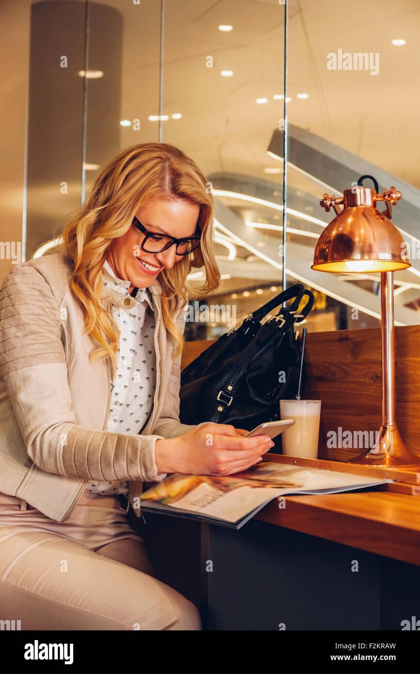 Mujer rubia sentada en una cafetería leyendo un mensaje de texto desde su smartphone Imagen De Stock