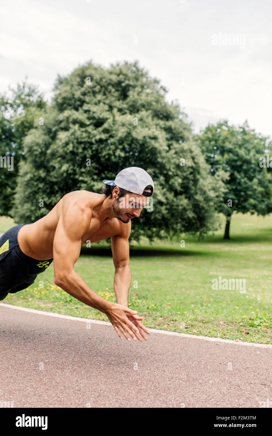 Joven atlético haciendo ejercicio en el parque Imagen De Stock