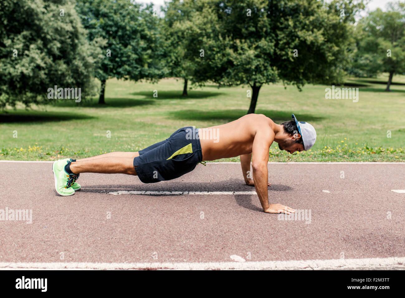 Joven haciendo pushups atlética en el parque Imagen De Stock