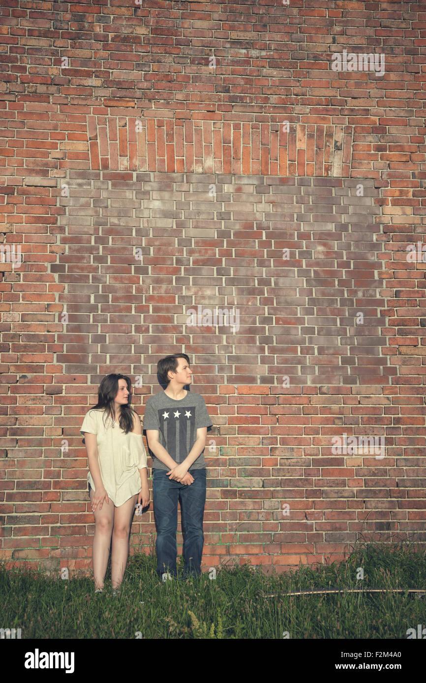 La pareja de adolescentes de pie delante de una pared de ladrillo Foto de stock