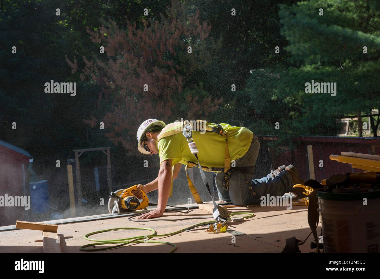 Carpenter utiliza una sierra circular para preparar la apertura de la ventana de instalación nuevo terreno común High School Foto de stock