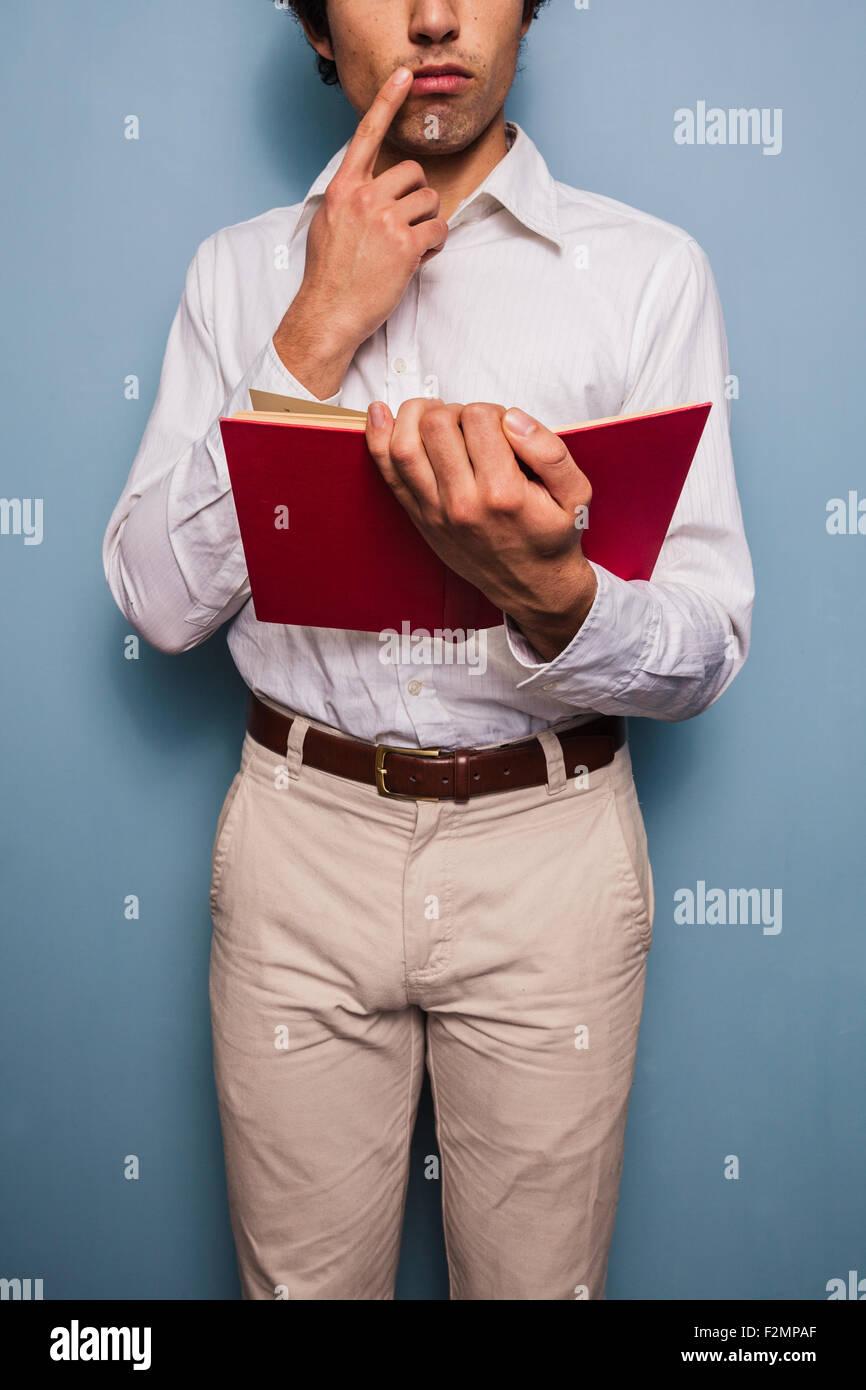 Joven parado por una pared azul libro de lectura Imagen De Stock