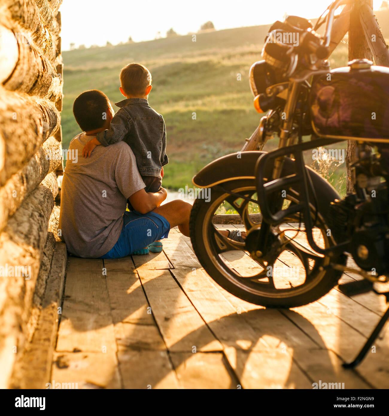 Mari, padre e hijo, sentado en el patio Foto de stock