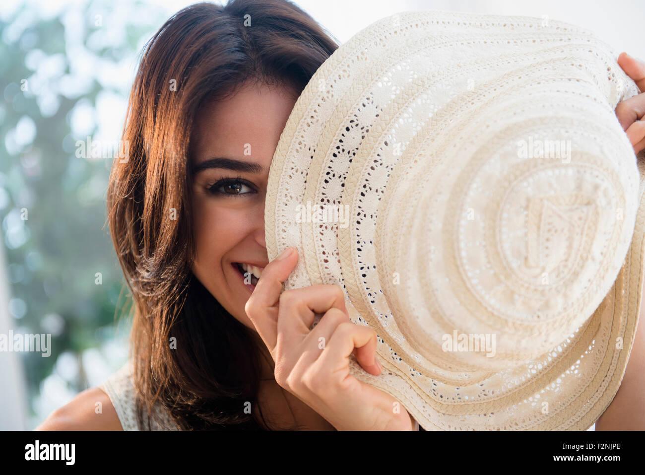 Cerca de mujer escondiéndose detrás de sombrero para el sol Foto de stock