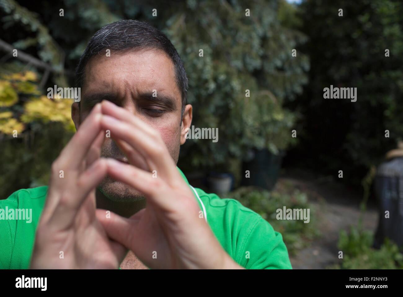 Hombre de raza mixta concentrado con las manos entrelazadas Foto de stock