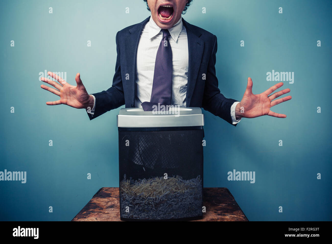 El empresario tiene su corbata atascado en una trituradora de papel Imagen De Stock