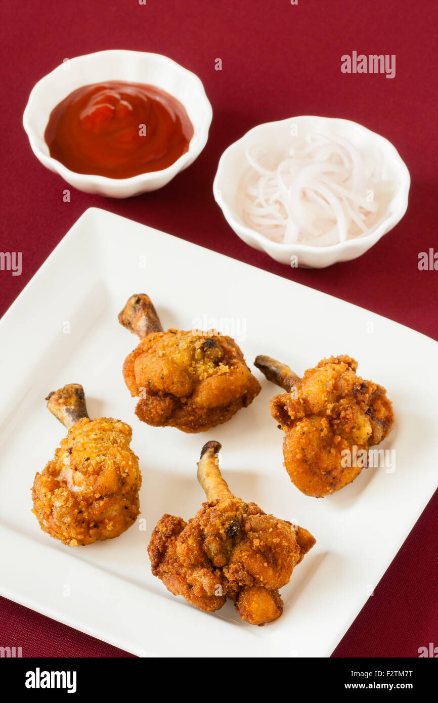 Acercamiento de Deep Fried Spicy Chicken lollipops servidos con tomate ketchup y cebolla cruda cadenas. DOF superficial. Imagen De Stock