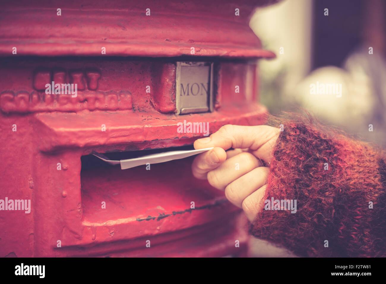 Primer plano de la mano de una mujer como ella es publicar una carta Imagen De Stock