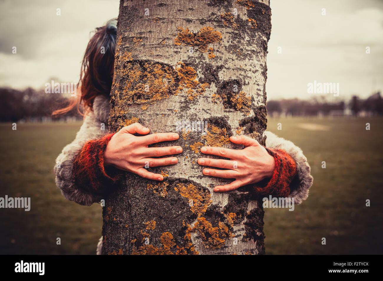 Mujer joven está en el parque en un día de invierno y está abrazando un árbol Foto de stock