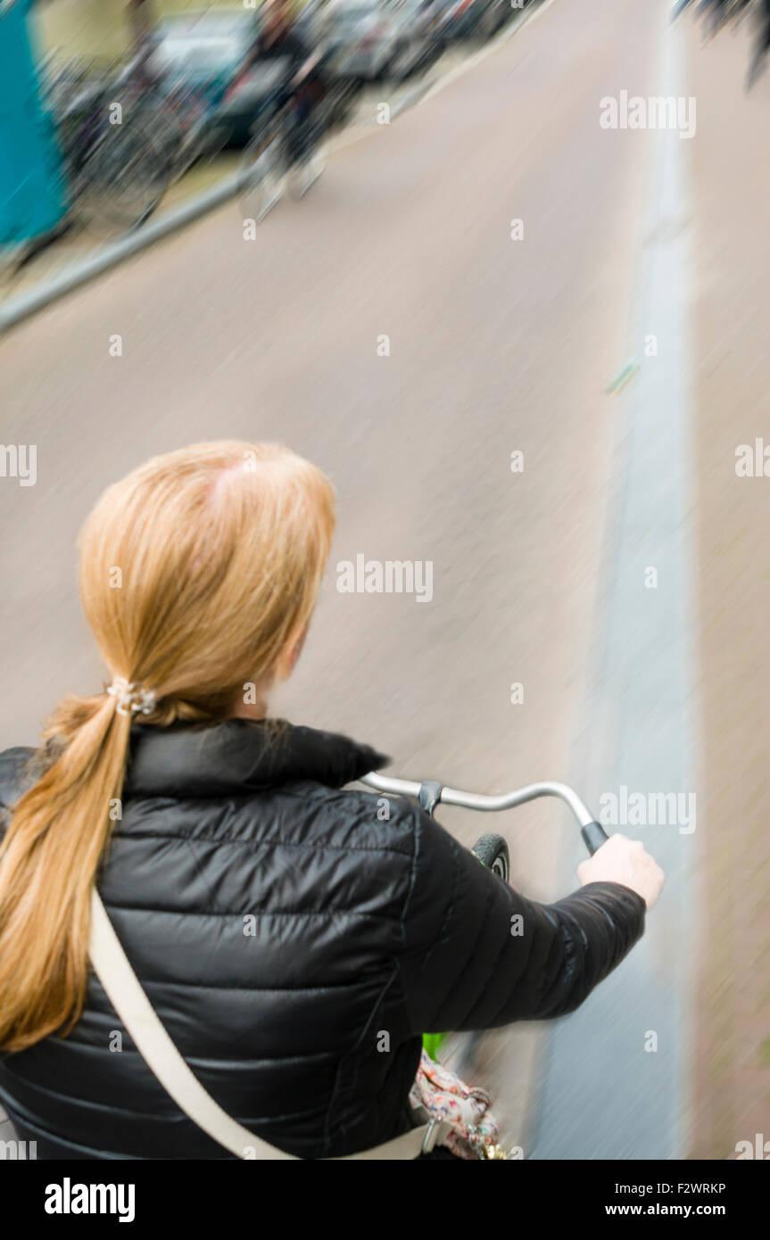 Una mujer paseos en bicicleta a lo largo de una calle en Amsterdam con el desenfoque de movimiento Foto de stock