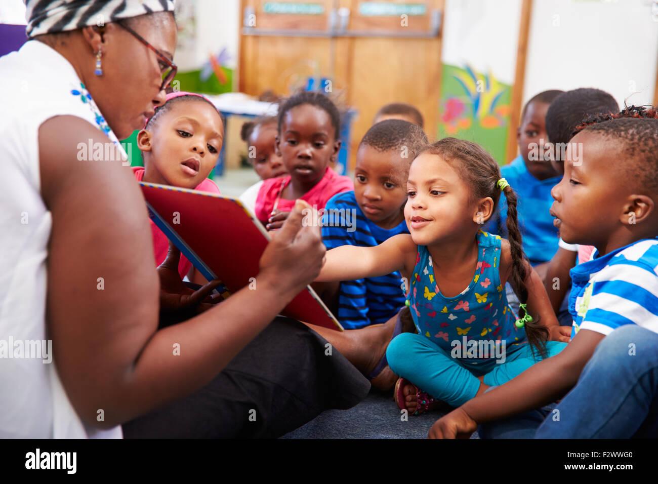 Maestra leyendo un libro con una clase de niños de edad preescolar Foto de stock