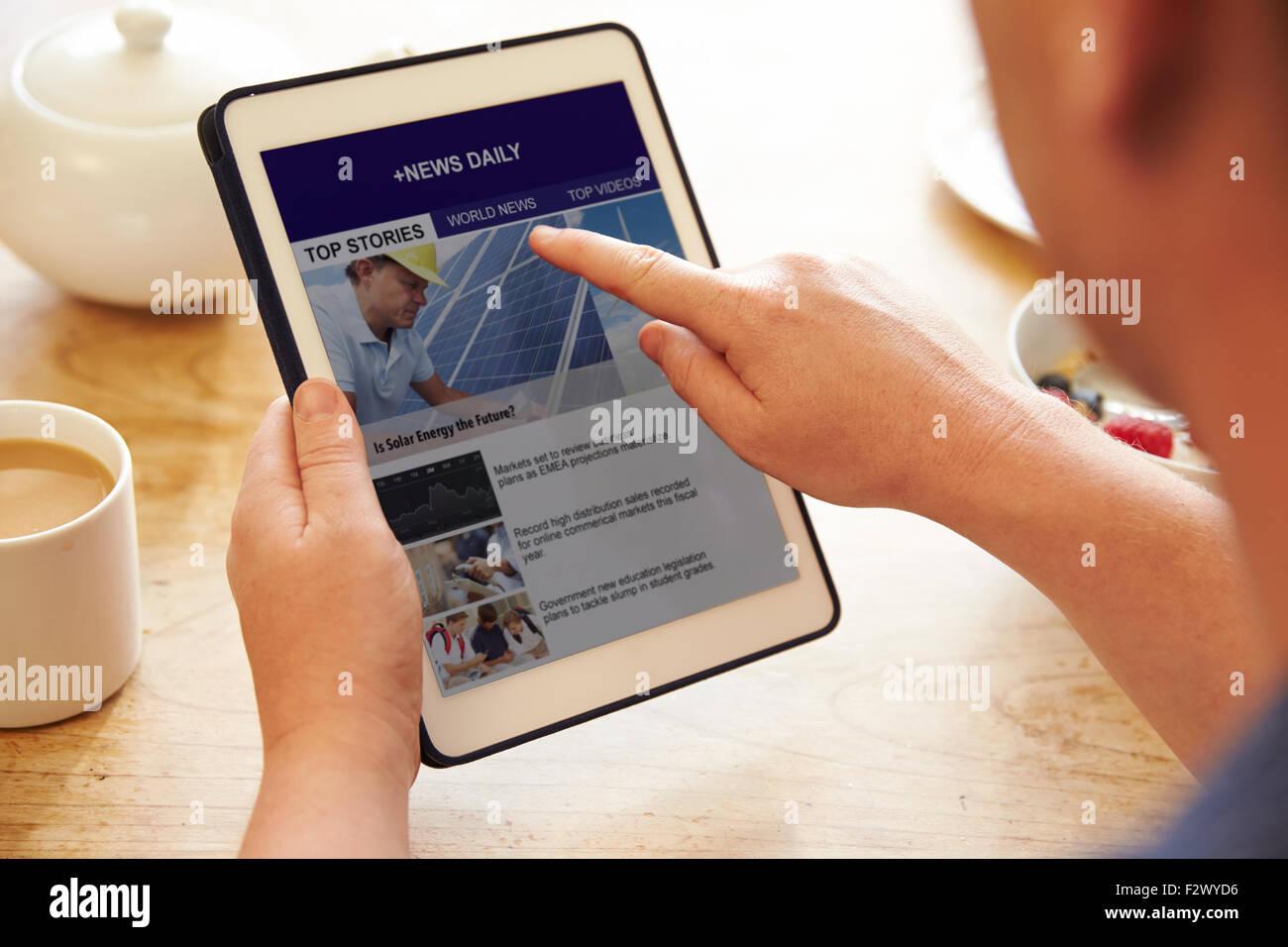 Persona en el desayuno mirando Noticias App en tableta digital Imagen De Stock