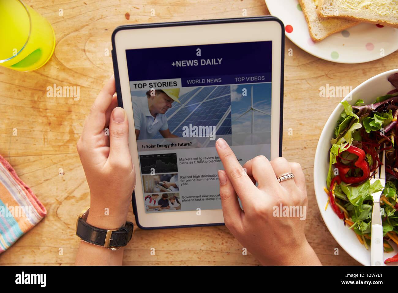 Persona en el almuerzo Mirando Noticias App en tableta digital Imagen De Stock