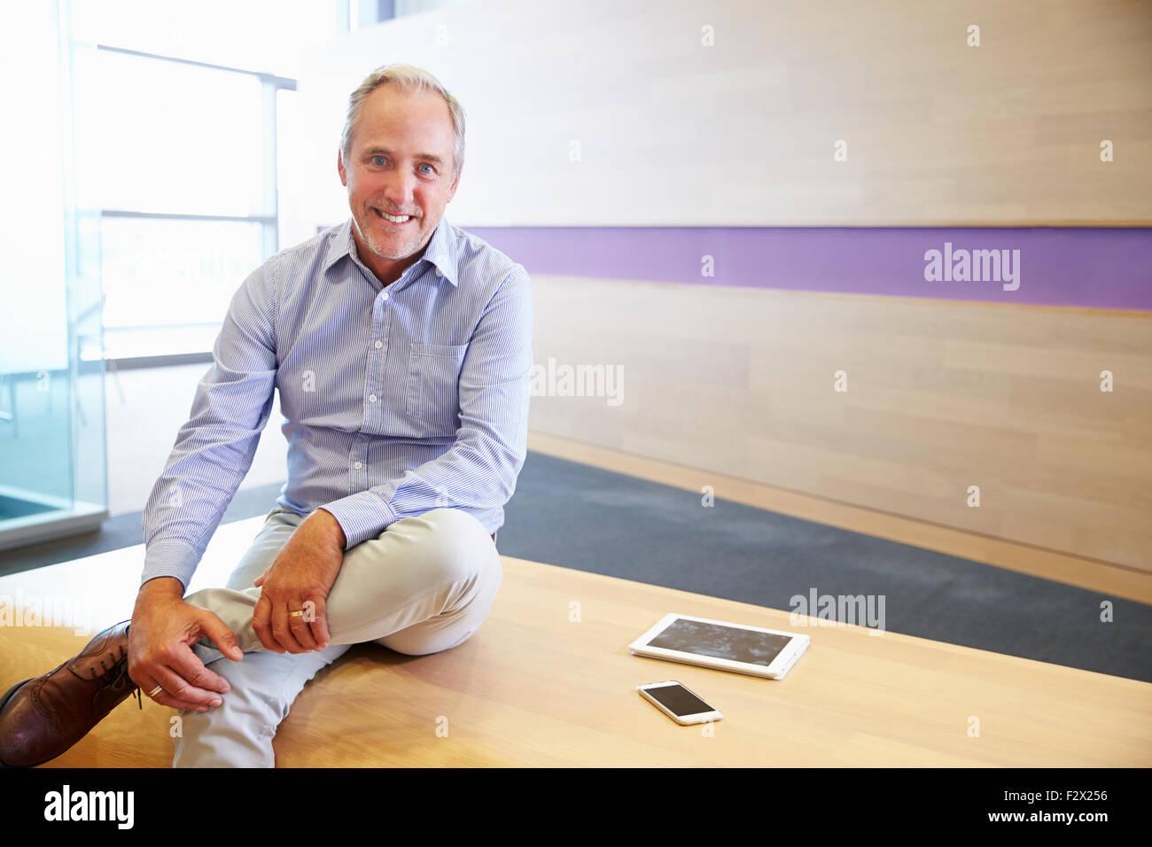 Smart casual hombre senior con Tablet PC y teléfonos inteligentes. Imagen De Stock