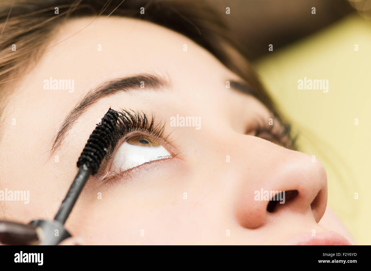 Closeup headshot morena recibiendo tratamiento por maquillaje estilista profesional aplicar mascara de pestañas Imagen De Stock