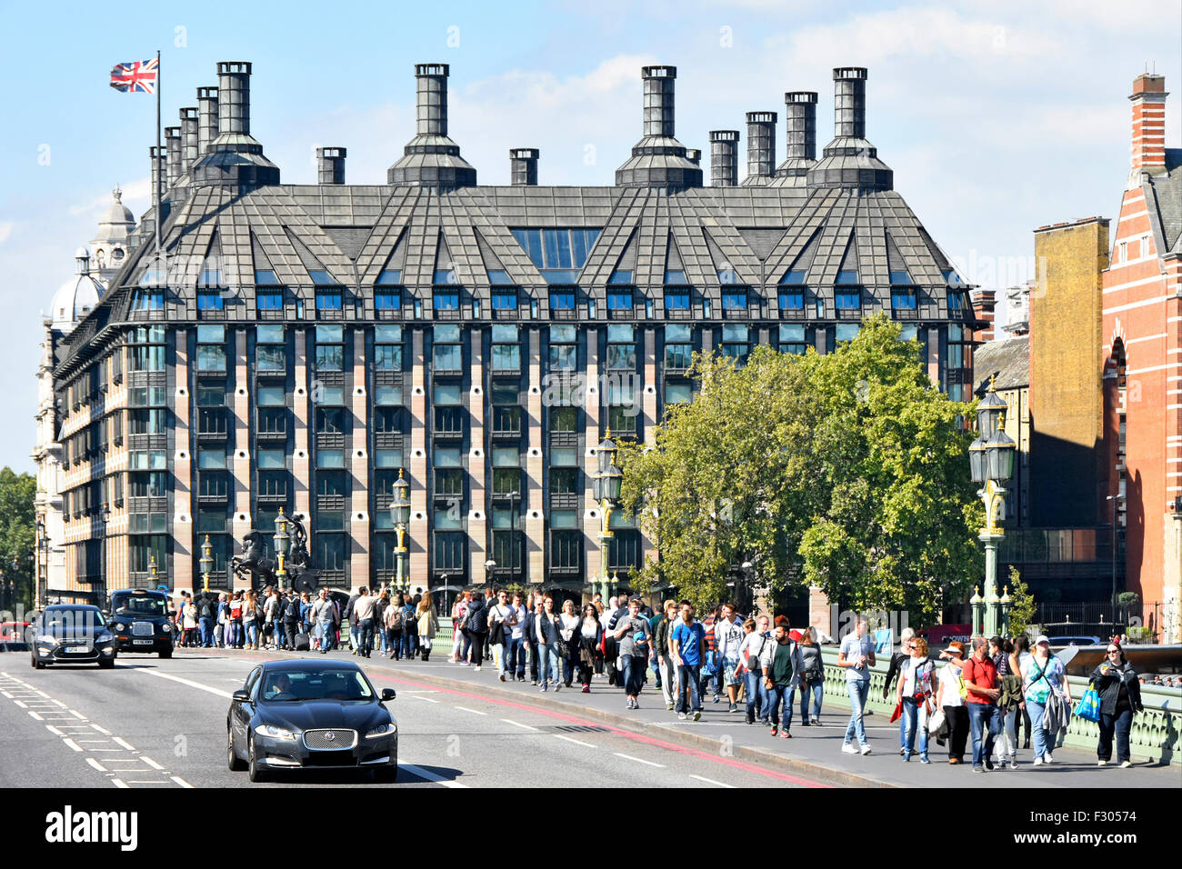 Portcullis House Londres complejo de oficinas para los miembros del Parlamento del Reino Unido con los turistas que caminan a lo largo de Westminster Bridge pavimento Inglaterra Foto de stock