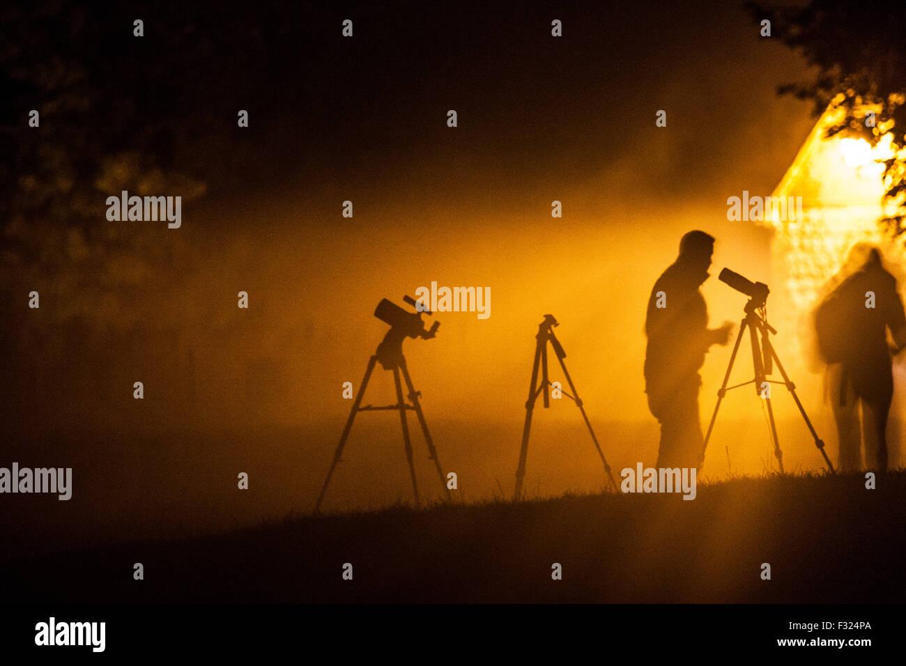 Las siluetas de los fotógrafos y trípodes esperando para fotografiar a la luna de sangre en Avebury. Imagen De Stock