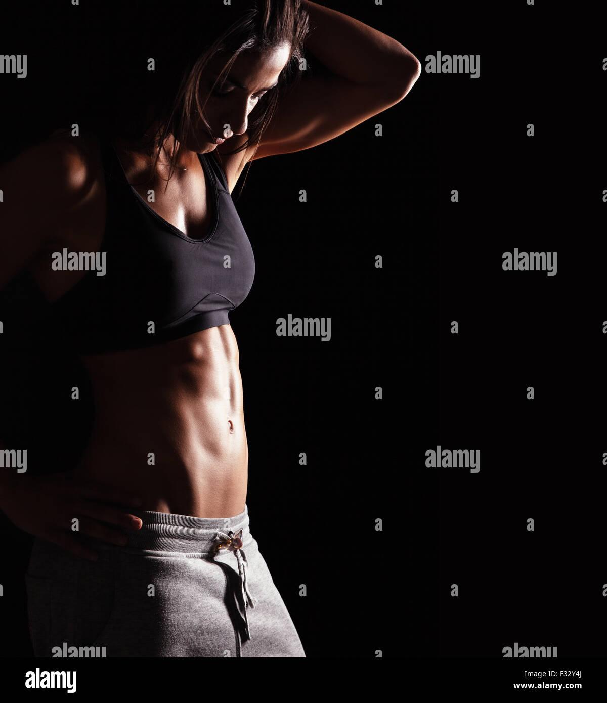 Imagen de mujer fitness en ropa deportiva mirando hacia abajo. Las hembras jóvenes de modelo con cuerpo musculoso. Imagen De Stock