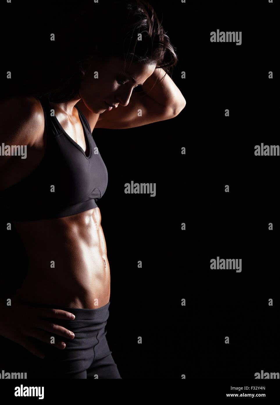 Colocar mujer con sus manos sobre las caderas. Hembra con cuerpo musculoso sobre fondo negro. Imagen De Stock