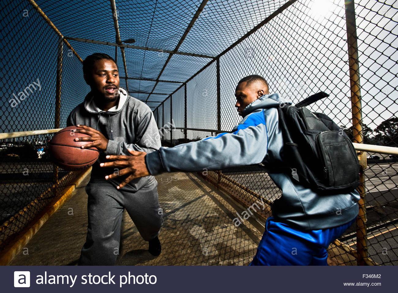 Dos chicos caminando por un puente de pie jugando con una pelota de baloncesto. Imagen De Stock