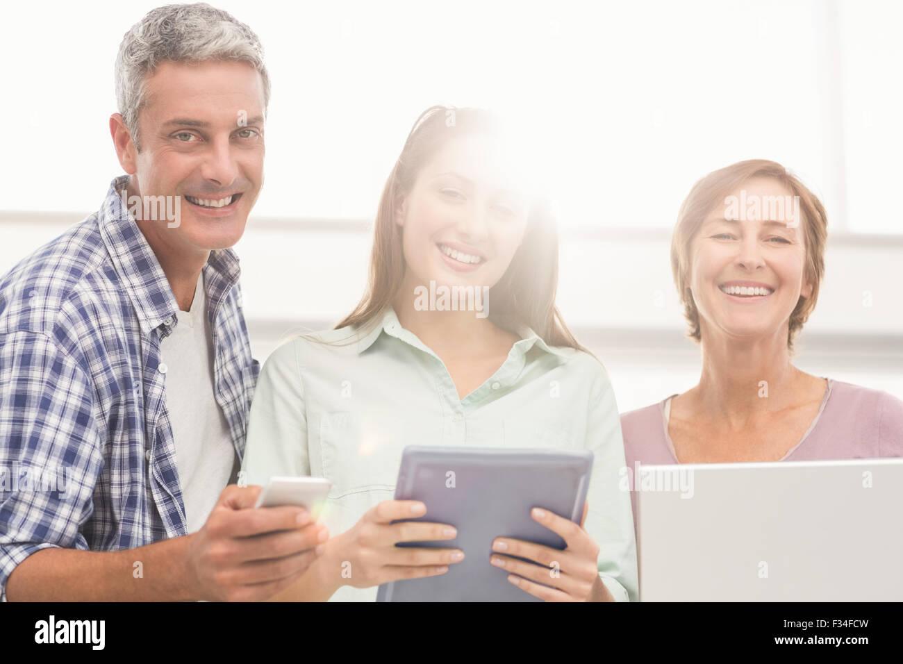 Gente de negocios informal con dispositivos electrónicos Foto de stock
