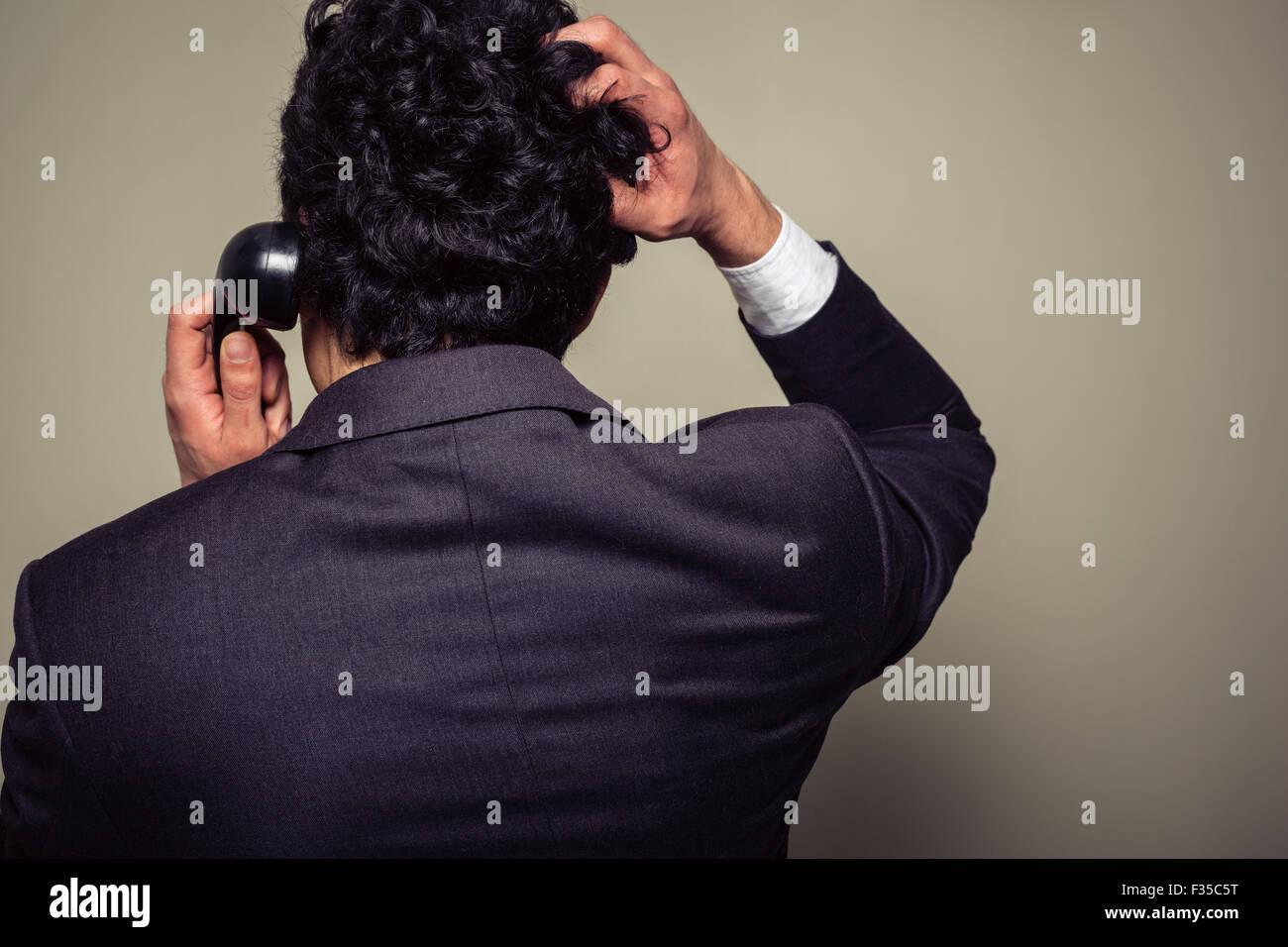 Vista trasera de un empresario confundido en el teléfono rascándose la cabeza Imagen De Stock