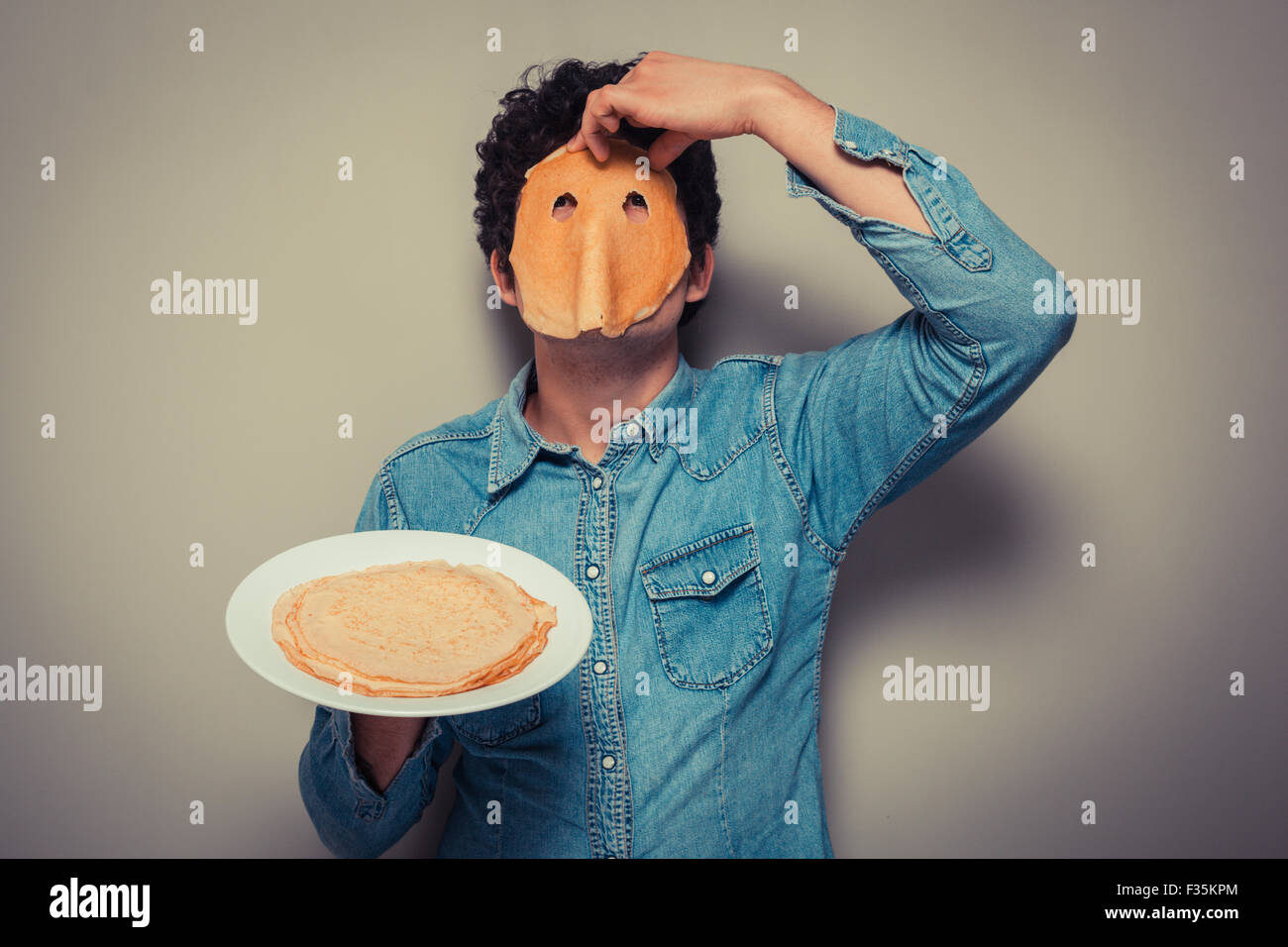 Eyeholes joven ha cortado en un panqueque y se lo lleva en su rostro. Imagen De Stock