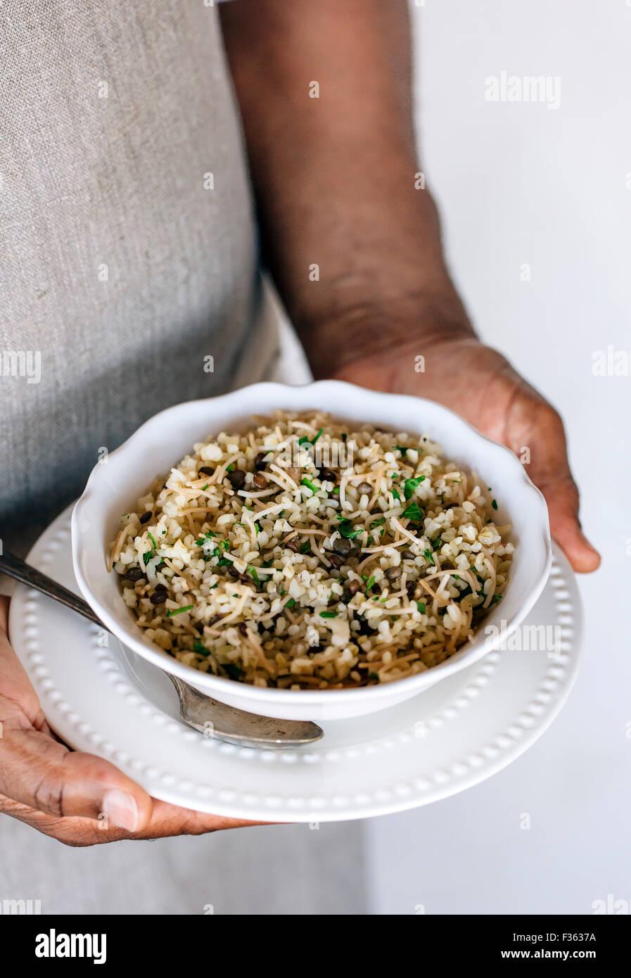 Un tazón de pilaf Bulgur mezclados con lentejas y hierbas frescas están en manos de un hombre vestido Imagen De Stock