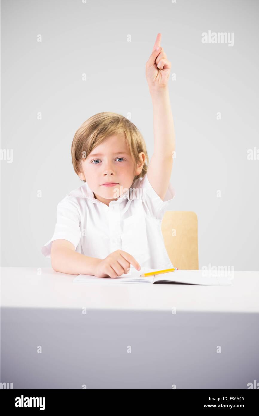 Imagen compuesta de lindo alumno levantando la mano Imagen De Stock