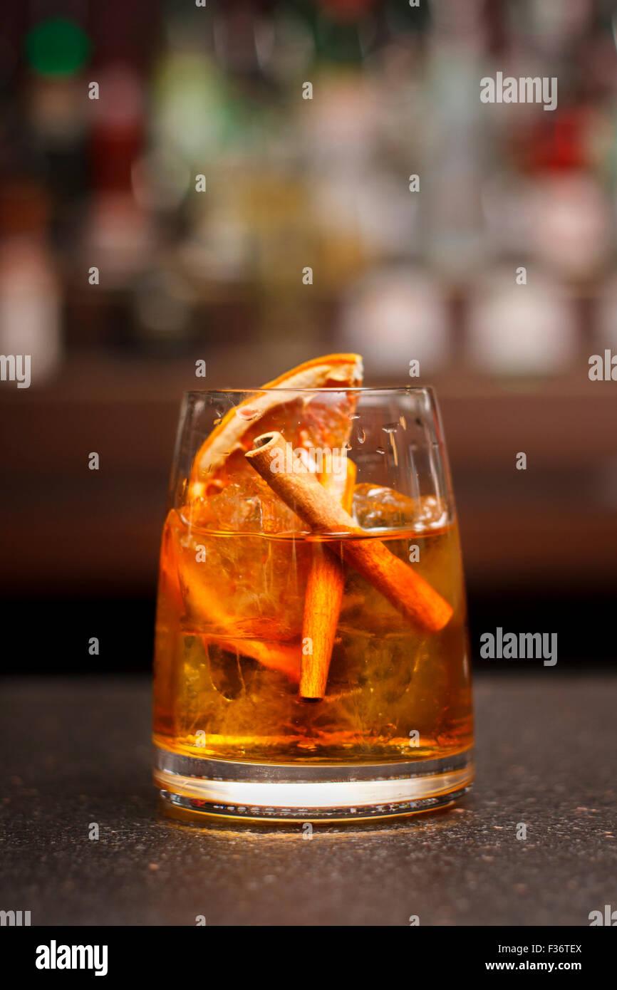 Old Fashioned cocktail con Secas de naranja y la ramita de canela Imagen De Stock