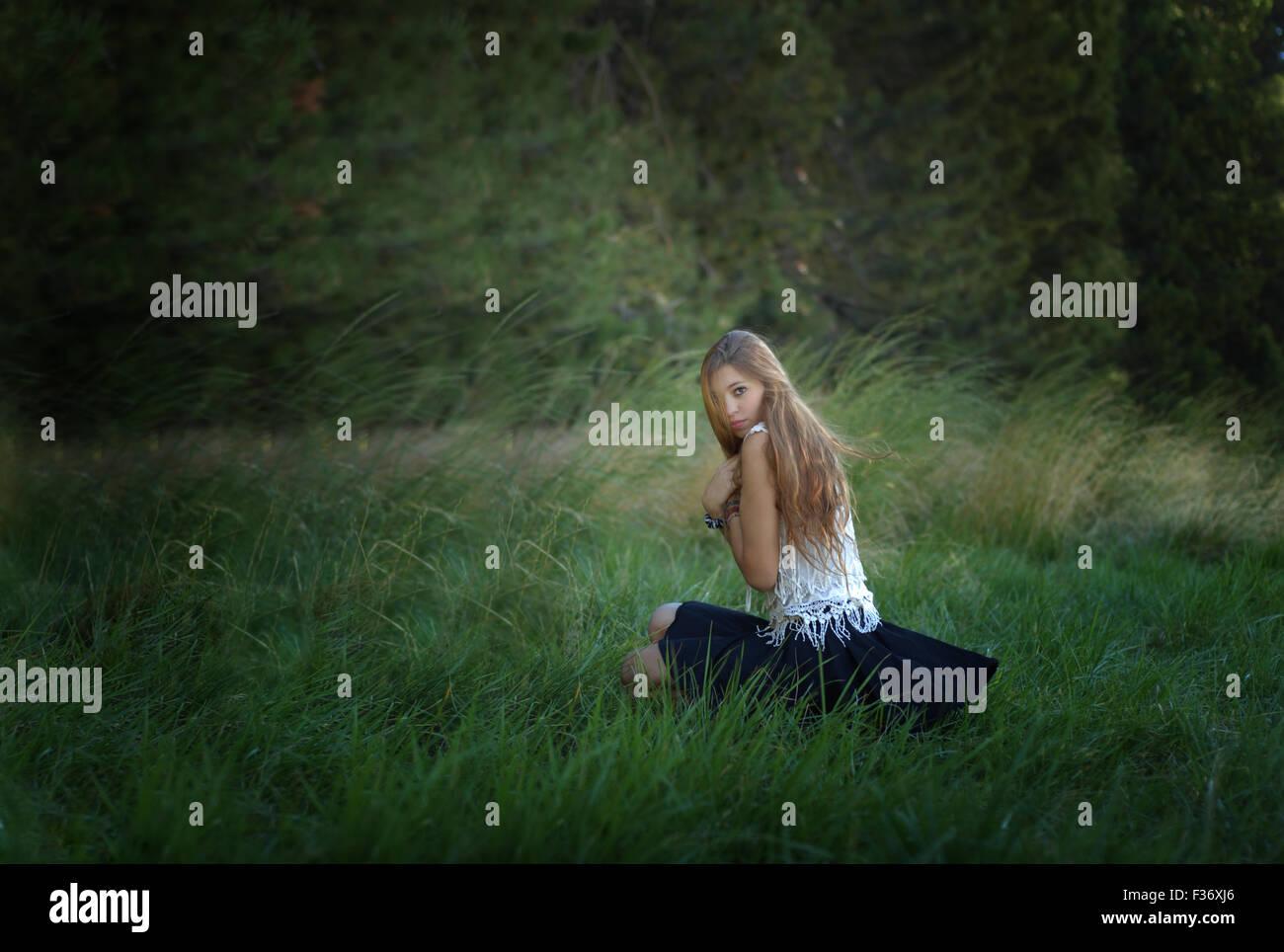 Misteriosa chica con el pelo largo en el bosque verde hierba Foto de stock
