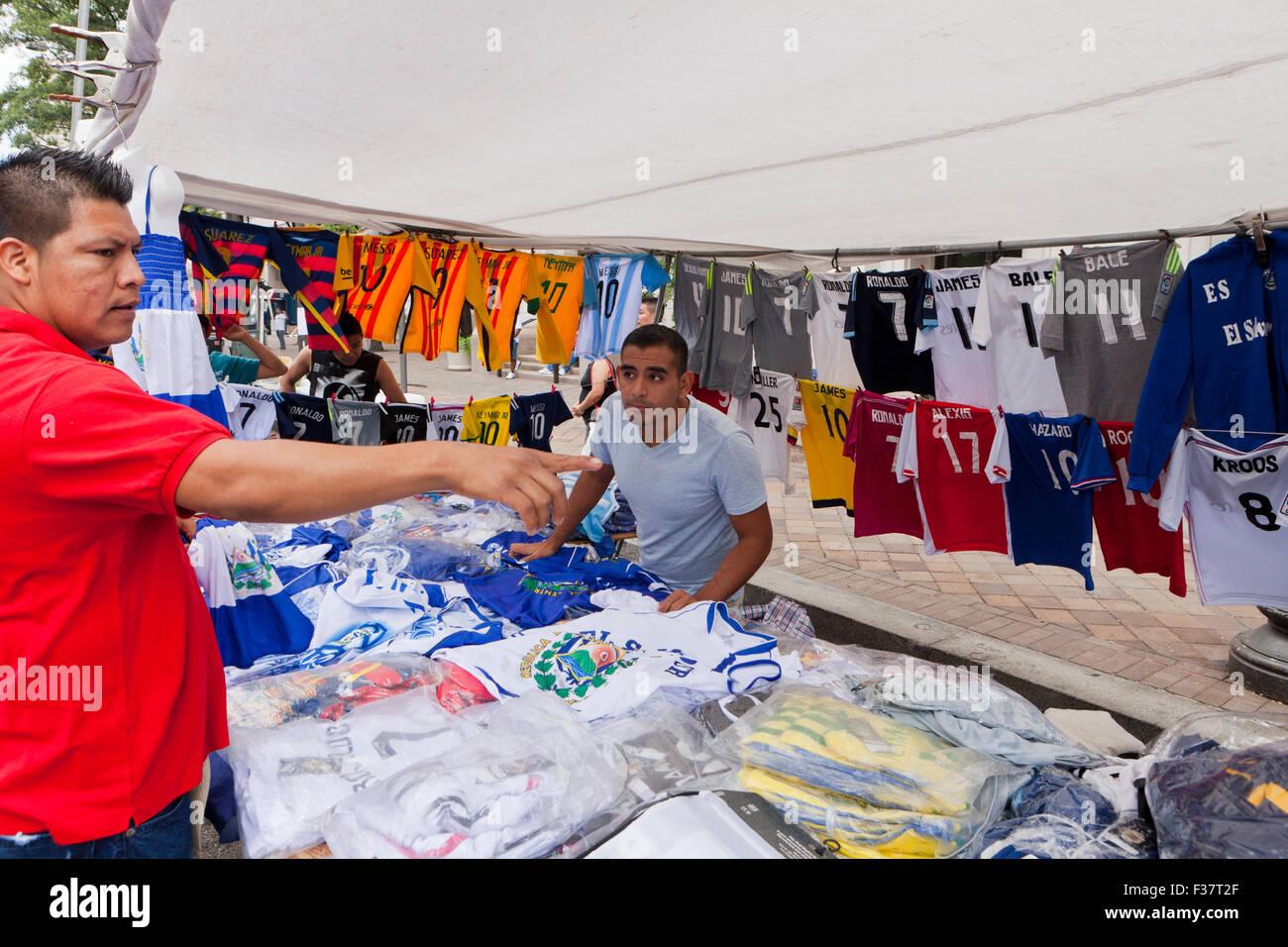 Hombre sacando ropa de fútbol jersey en tienda de campaña en un festival al aire libre - EE.UU. Imagen De Stock