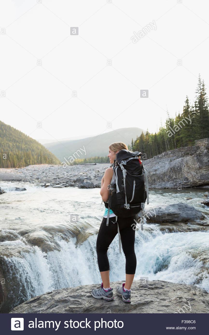 Excursionista hembra con mochila de pie en escarpada cascada Imagen De Stock