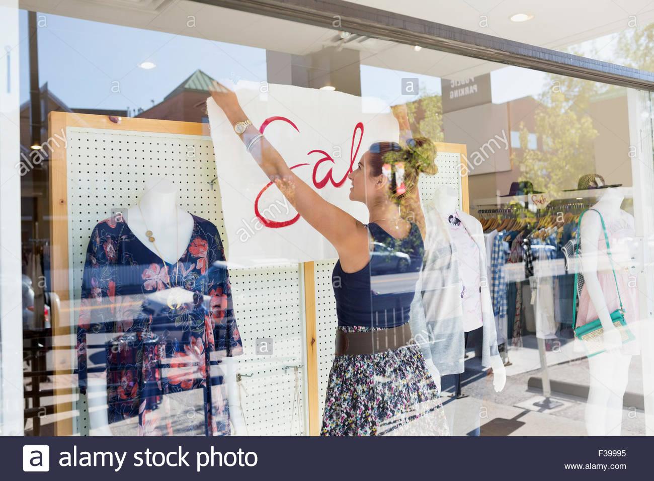 Trabajador venta firmar tienda de ropa colgando de la ventana Imagen De Stock