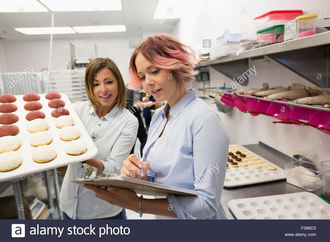 Pasteleros con pastelitos y portapapeles cocina comercial Imagen De Stock