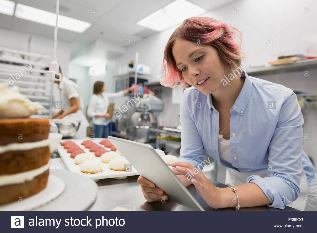 Chef de repostería con tableta digital en cocina comercial Imagen De Stock