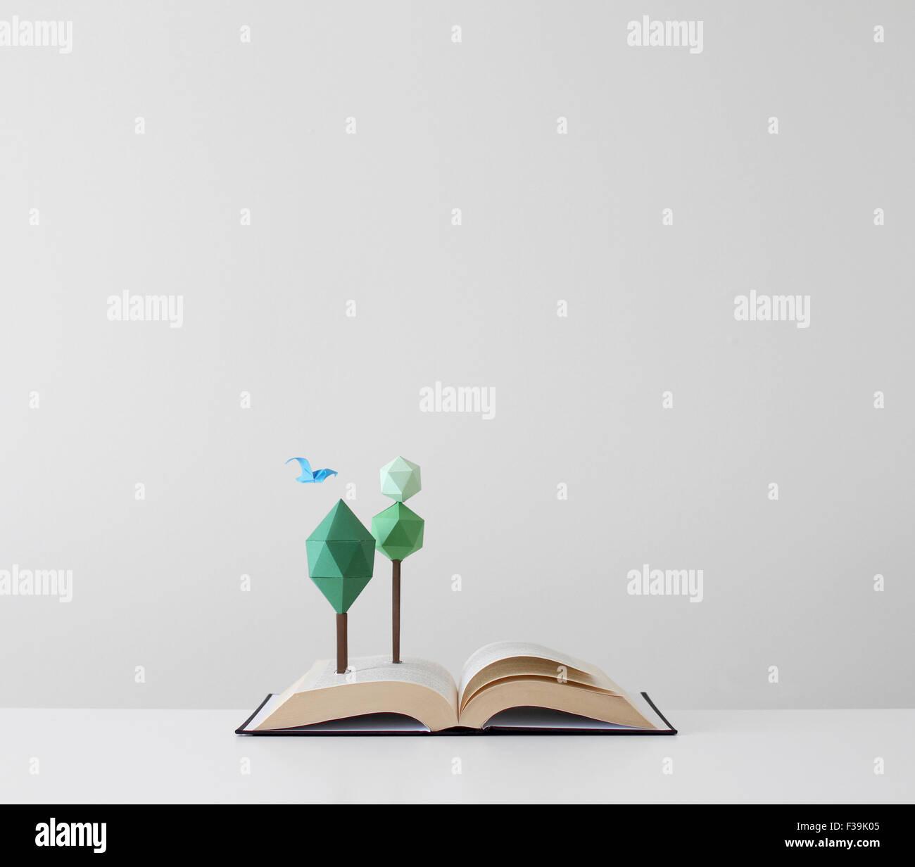 Aves y árboles que crecen fuera de un libro abierto Imagen De Stock