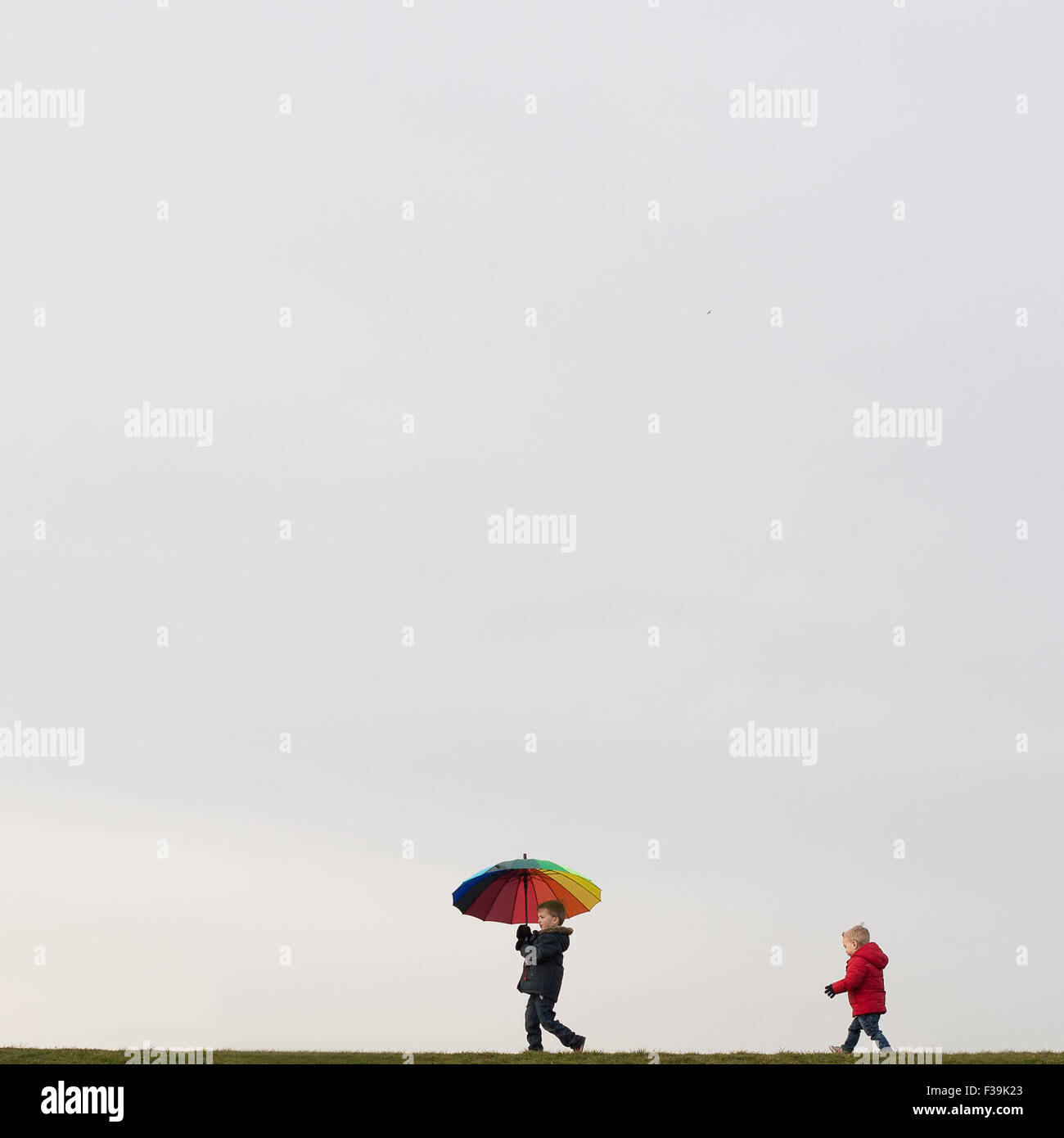Niños caminando, sosteniendo un paraguas Imagen De Stock