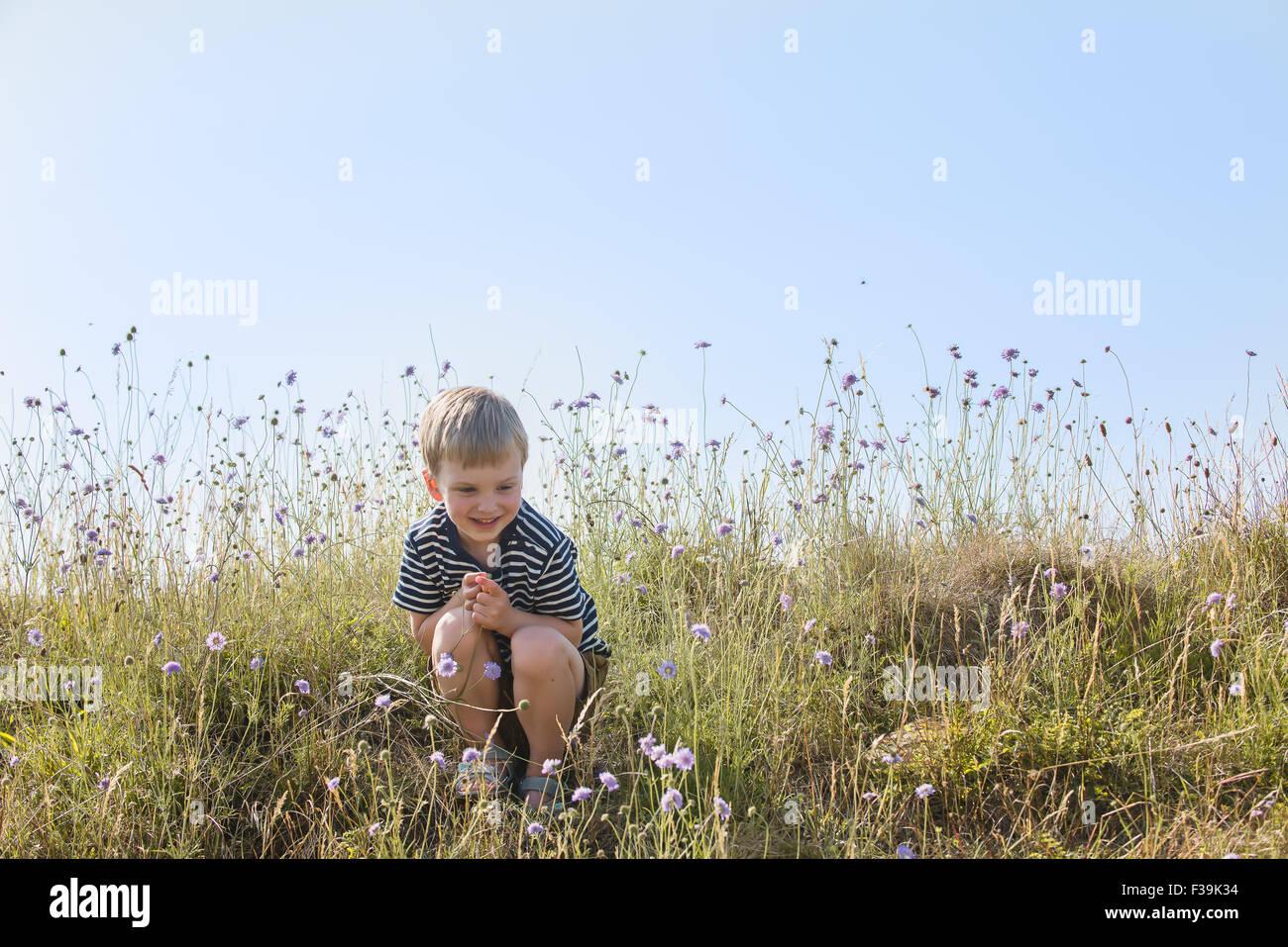 Muchacho sentado en campo verde, sonriendo Imagen De Stock