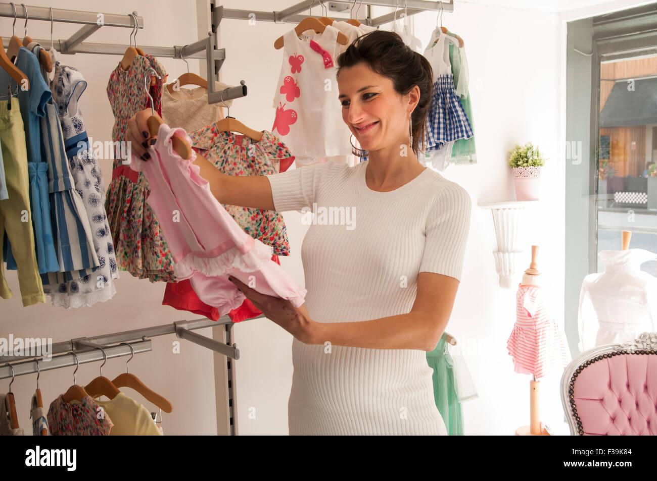 Retrato de una mujer embarazada sonriendo mirando en una tienda de ropa para bebés Imagen De Stock