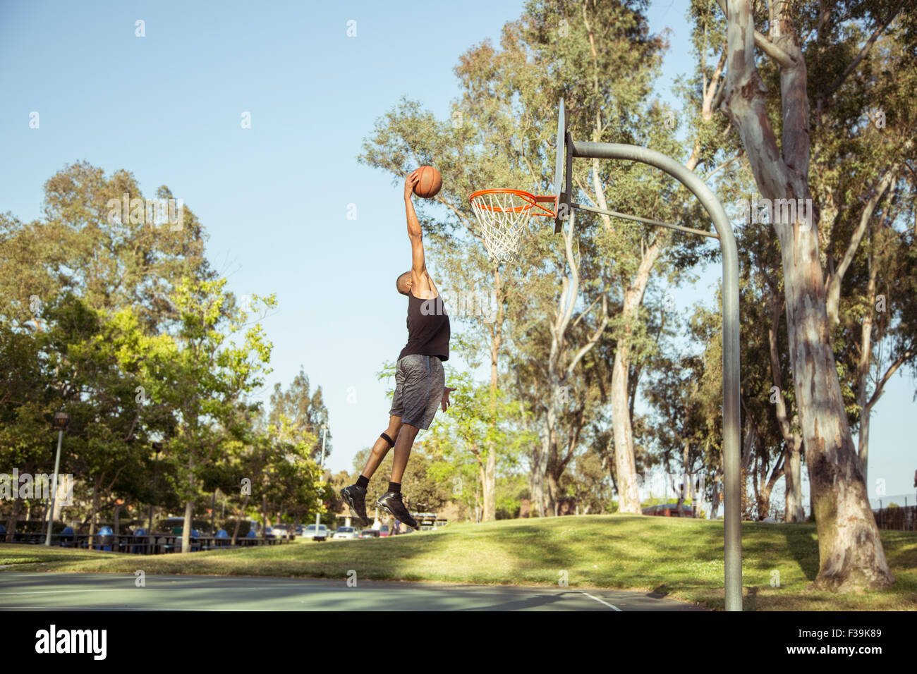 Hombre disparar aros de baloncesto en el parque al atardecer Imagen De Stock